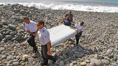 Полицейские несут обломки самолета, найденные в Сен-Андре, Реюньон