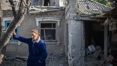 Женщина у поврежденного в результате обстрела дома в поселке Александровка. Архивное фото