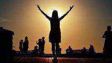 Девушка любуется закатом над морем на Приморском бульваре в Севастополе