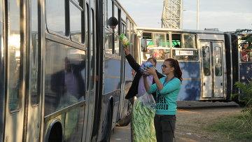 Волонтеры передают воду беженцам, ожидающим отправки в миграционный лагерь. Архивное фото