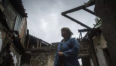 Ольга Бубнова во дворе своего дома, который был разрушен в результате попадания снаряда, в Донецке