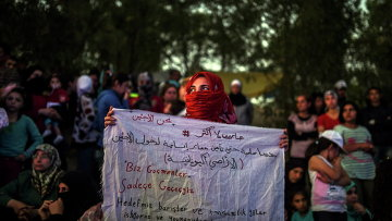 Сирийская женщина с плакатом Мы мигранты, мы пройдем на пути к греческой границе