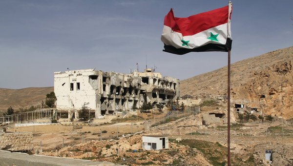 Сирийский флаг на фоне разрушенного дома в сирийском городе Маалюля. Архивное фото