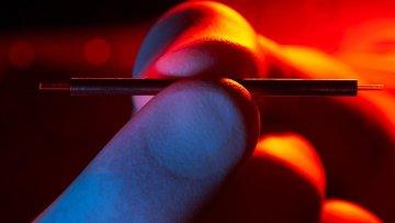 Ученый держит миниатюрный ускоритель частиц в руке