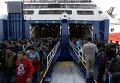 Мигранты прибывают в порт города Афины, Греция