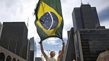 Мужчина размахивает флагом Бразилии во время акции протеста в Сан-Паулу. 13 декабря 2015