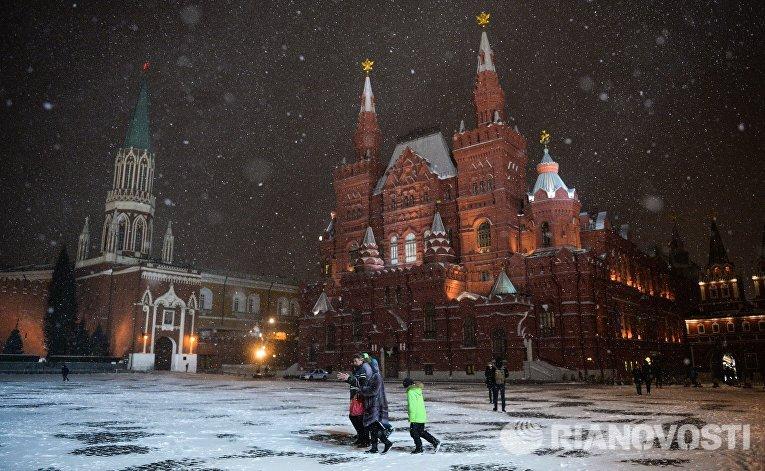 Прохожие во время снегопада на Красной площади в Москве