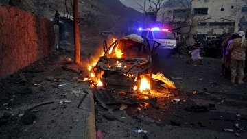 Горящий автомобиль после взрыва у дома главы службы безопасности Йемена. 17 января 2016