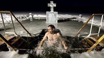 Мужчина во время купания в озере Валдайского Иверского Святоозерского монастыря