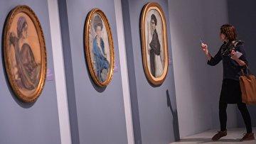 Посетительница у картин Портрет Г.Л.Гиршман, 1911, Портрет Е.П.Олив, 1909 и Портрет С.В.Олсуфьевой, 1911 на открытии выставки Валентин Серов