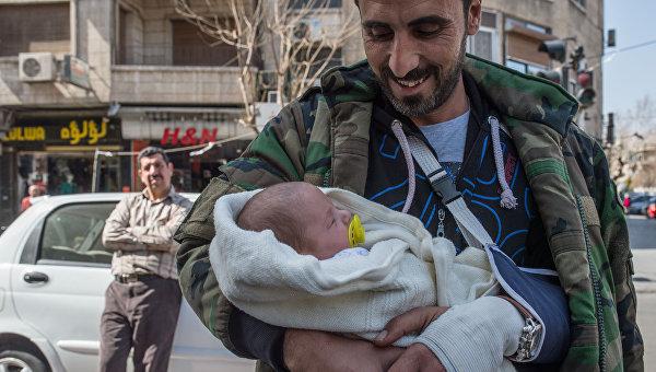 Мужчина с грудным ребенком на улице Дамаска в первый день перемирия. Архивное фото