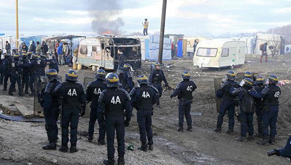 Сотрудники полиции в лагере мигрантов возле Кале, Франция