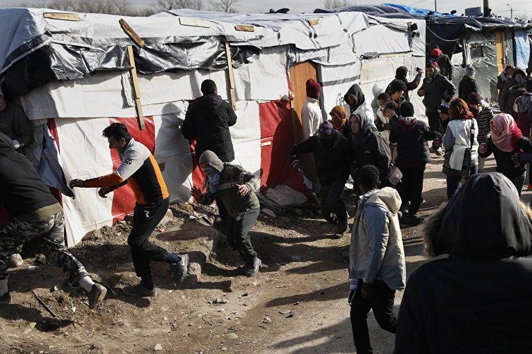 Сотрудники полиции применили слезоточивый газ во время беспорядков в лагере мигрантов Джунгли возле Кале, Франция. 29 февраля 2016
