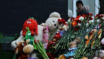Цветы и игрушки в память об убитой девочке возле подъезда дома на улице Народного ополчения в Москве