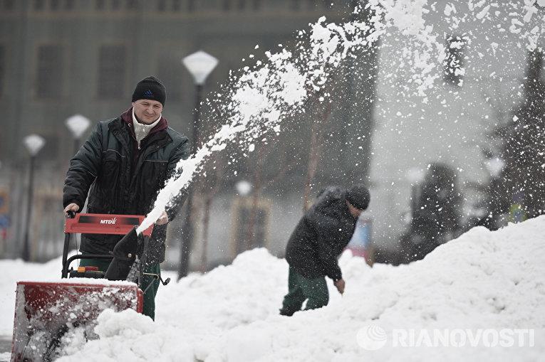 Мужчина убирает снег с помощью снегоуборочной машины после сильного снегопада в Москве
