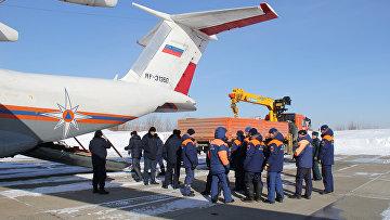 Погрузка оборудования и посадка спасателей МЧС России в самолет, вылетающий на Оху