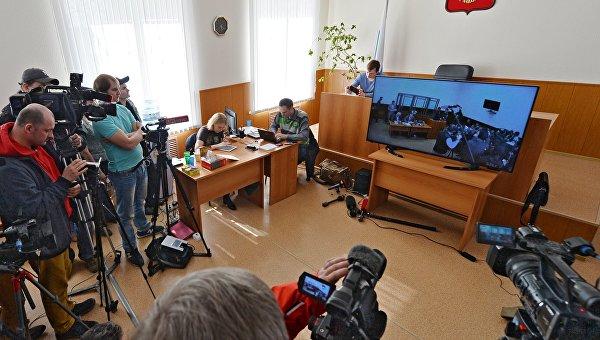 Журналисты смотрят на экране монитора трансляцию заседания по делу украинской летчицы Надежды Савченко