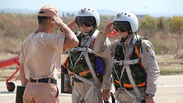 Российские летчики принимают рапорт у командира техников перед полетом на авиабазе Хмеймим в Сирии