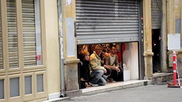 Прохожие в укрытии неподалеку от места взрыва на улице Истикляль в Стамбуле. 19 марта 2016