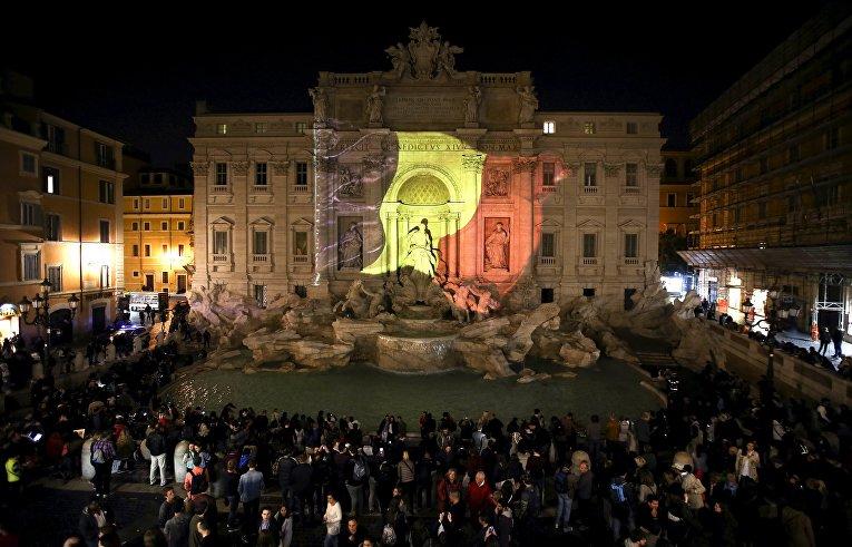 Цвета бельгийского флага на фасаде фонтана Треви в память о жертвах терактов. Рим, Италия