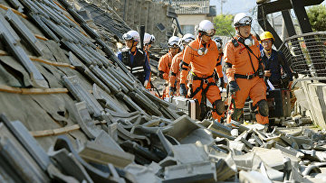 Пожарные среди разрушенных в результате землетрясения зданий. Кумамото, Япония. Апрель 2016