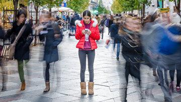 Девушка с телефоном на улице. Архивное фото