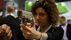 Женщина держит пистолет во время выставки SOFEX-2016 в Аммане, Иордания