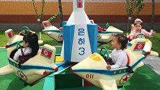 Дети катаются на карусели в виде северокорейского спутника Ынха-3 (Млечный путь-3) в одном из детских садов Пхеньяна