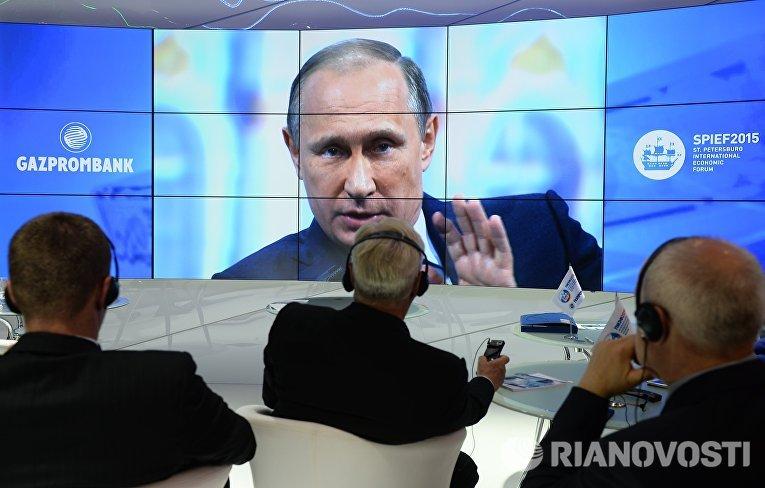 Участники XIX Петербургского международного экономического форума смотрят трансляцию выступления президента РФ Владимира Путина на панельной дискуссии в ходе пленарного заседания ПМЭФ