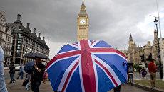 Человек с зонтом с флагом Великобритании у Биг Бена и здания парламента в Лондоне. Архивное фото