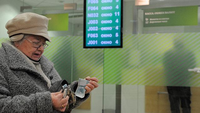 Женщина считает деньги в отделении Сбербанка России. Архивное фото