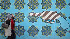 Женщины идут вдоль стены здания бывшего посольства США в Тегеране. Архивное фото