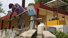 Местный житель набирает воду из источника в Котле, Индия