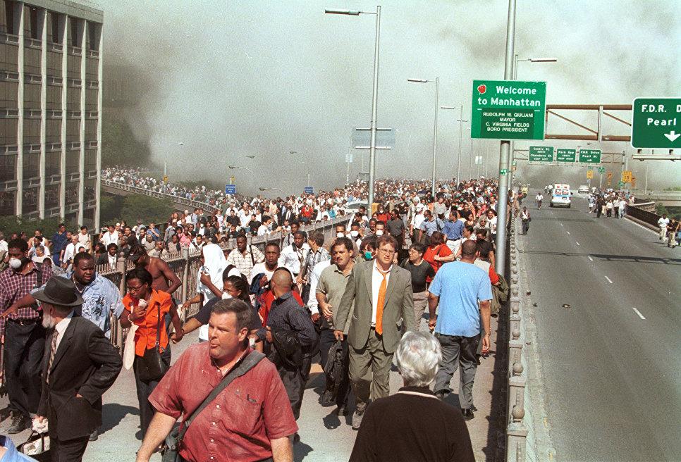 Люди бегут по Бруклинскому мосту после террористической атаки на Всемирный торговый центр в Нью-Йорке. 11 сентября 2001