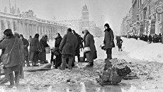 Жители блокадного Ленинграда набирают воду, появившуюся после артобстрела в пробоинах в асфальте