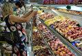 """Покупательница у прилавка с фруктами в гипермаркете """"Лента"""" в Новосибирске"""
