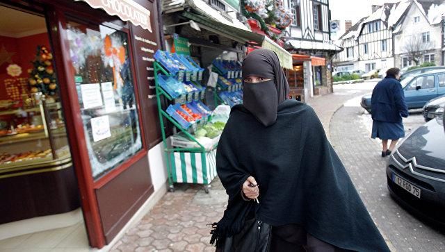 Девушка в мусульманской одежде на улице Ле Мениль-Сен-Дени, Франция. Архивное фото