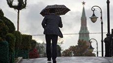 Мужчина на Лужковом мосту во время дождя в Москве. Архивное фото