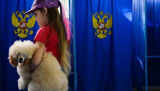 Девочка с собакой в единый день голосования на избирательном участке в Новосибирске