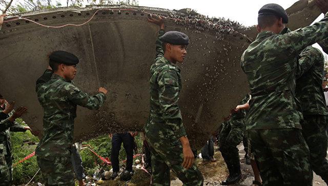Тайские полицеские рядом с обломком, который нашли у побережья южной части Таиланда. 23 января 2016 года