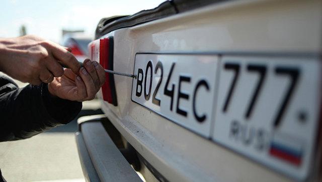 Крепление автомобильного номера к машине. Архивное фото