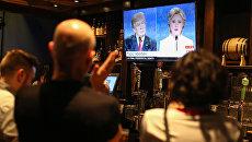Люди смотрят трансляцию дебатов между Дональдом Трампом и Хиллари Клинтон. 19 октября 2016