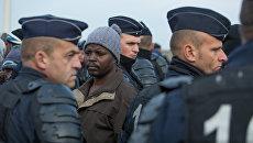 Беженцы в специально организованном центре по распределению мигрантов CAO рядом с лагерем Кале во Франции. Архивное фото