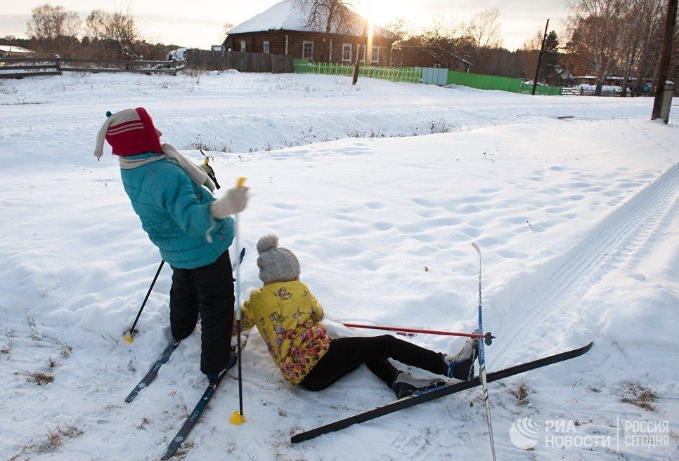 Дети катаются на лыжах в заснеженном селе Березовка в Томской области