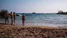 Туристы на берегу Средиземного моря в городе Протарас на Кипре
