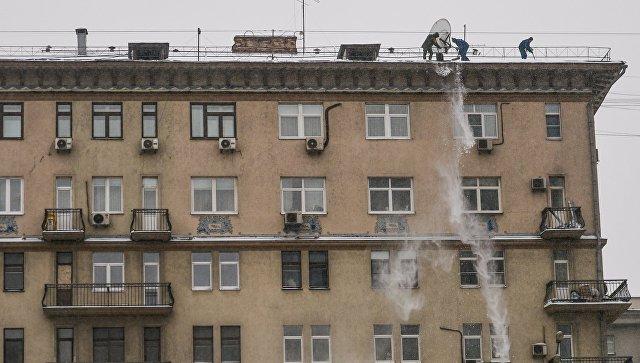 Работники служб ЖКХ сбрасывают снег с крыши одного из домов на Смоленском бульваре в Москве