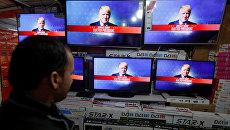 Мужчина смотрит трансляцию объявления результатов голосования на выборах президента США в Кабуле