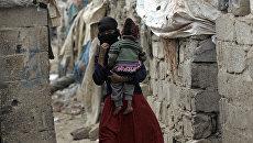Женщина из сообщества Ахдам с ребенком в городе Сана, Йемен. Архивное фото