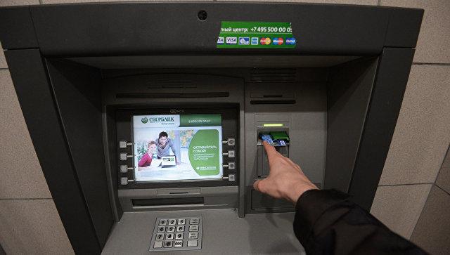 Клиент у банкомата Сбербанка в Москве. Архивное фото