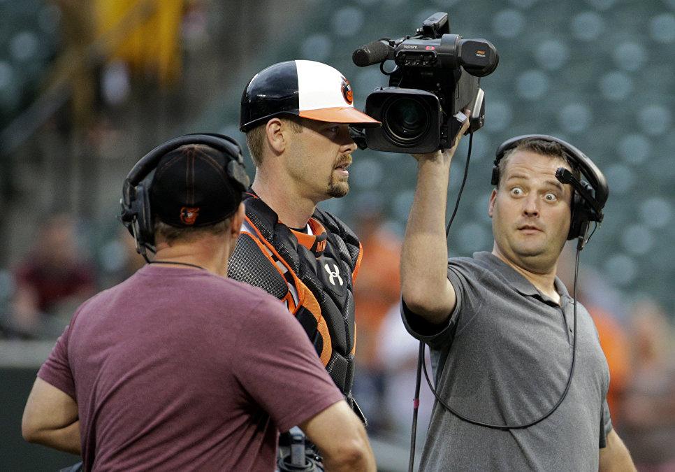 Телеоператор снимает бейсболиста Мэтта Уиетерса во время матча между Балтимор Ориолс и Нью-Йорк Янкиз в Балтиморе, США